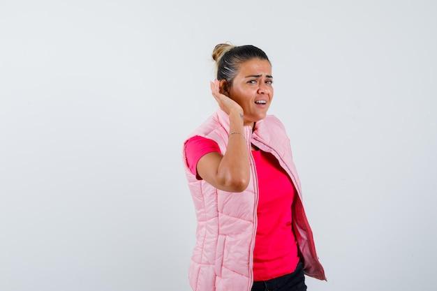 Femme gardant la main derrière l'oreille en t-shirt, gilet et à la confusion