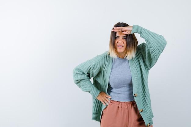 Femme gardant la main sur la tête dans des vêtements décontractés et à la vue de face, focalisée.