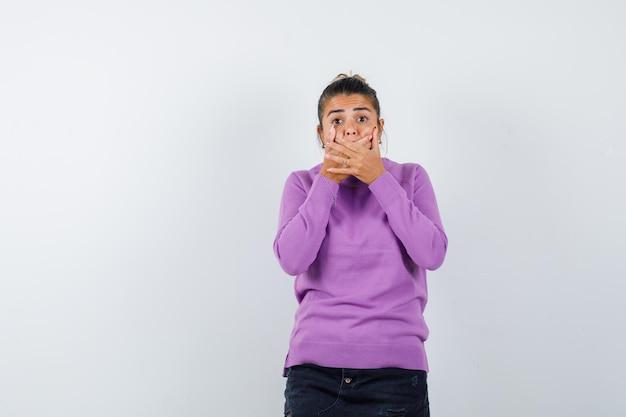 Femme gardant les mains sur la bouche en blouse de laine et à la peur