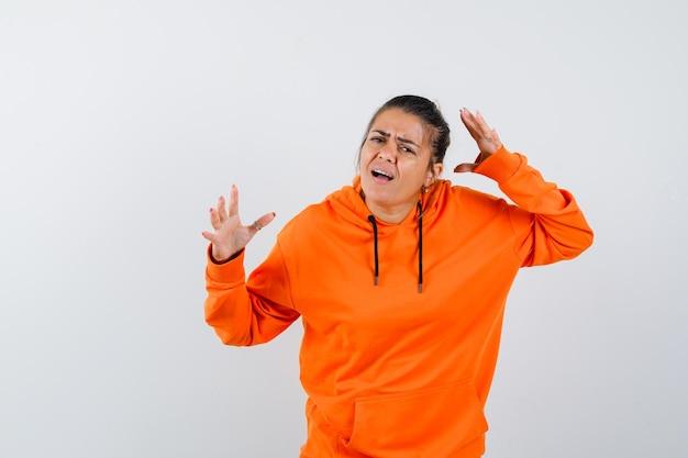 Femme gardant les mains dans un geste perplexe en sweat à capuche orange