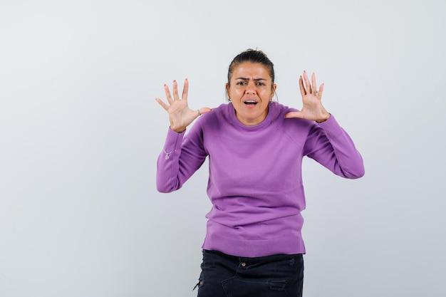 Femme gardant les mains levées, ayant des problèmes d'audition en chemisier en laine et ayant l'air confus