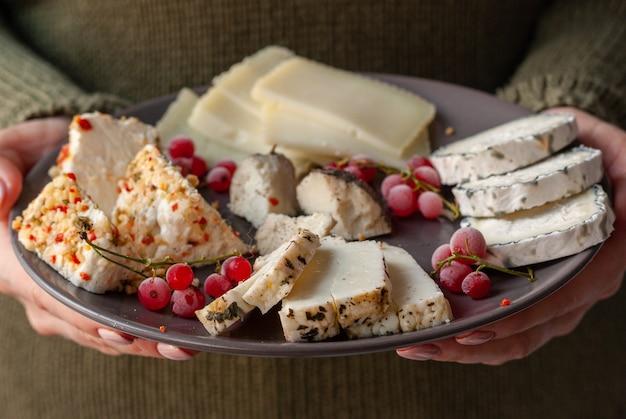 Femme garde dans ses mains assiette en céramique sombre avec un assortiment de fromages de chèvre fermier