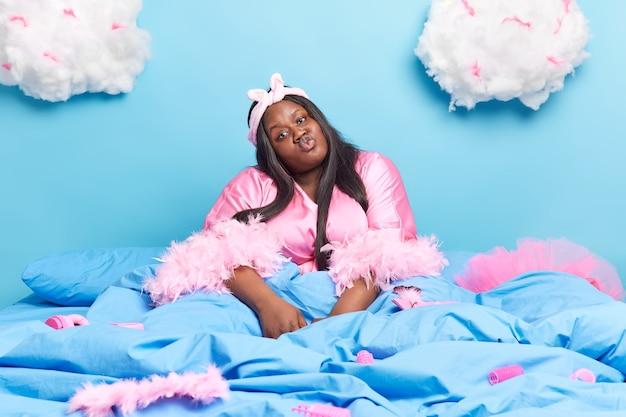 Une femme garde les lèvres pliées veut embrasser son mari a une journée de farniente à la maison vêtue de vêtements domestiques pose sur un lit confortable sous une couverture avec différents objets autour