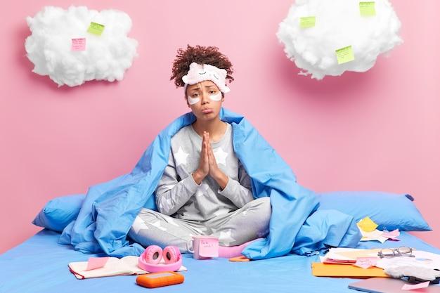 La femme garde les paumes ensemble dans le geste de prière porte des vêtements de nuit est assise les jambes croisées pose sur un lit confortable entouré d'autocollants en papier isolés sur rose