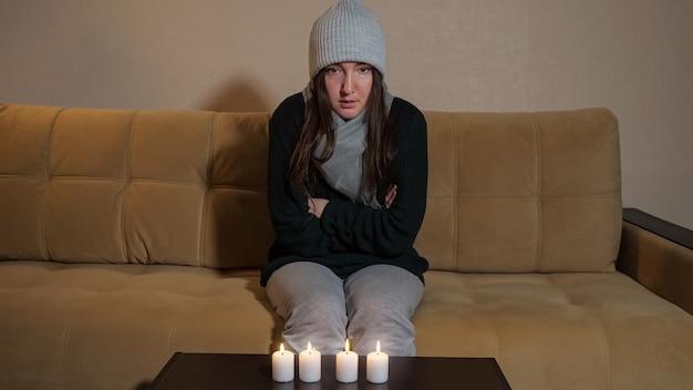 Une femme gelée essaie de chauffer les mains sur des bougies allumées sur un canapé