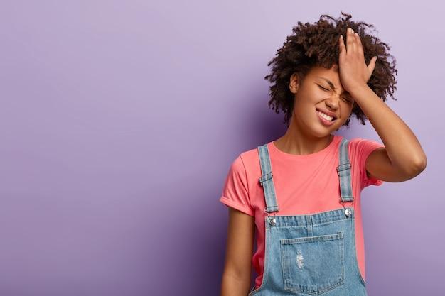 Femme gênante déçue garde la paume sur le front, les regrets ont fait quelque chose de mal, face à une situation problématique, habillé en otfit à la mode, pose sur purple wal