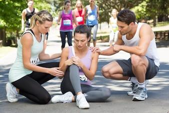 Femme avec un genou blessé pendant la course dans le parc