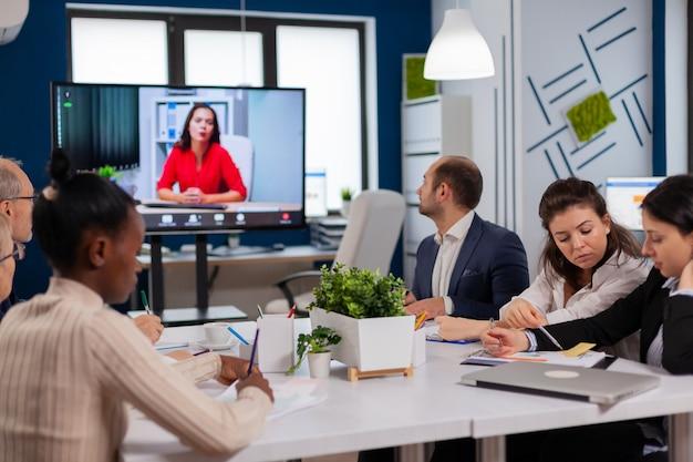 Femme gestionnaire assise devant la caméra parlant lors d'un appel vidéo lors d'une conférence virtuelle travaillant