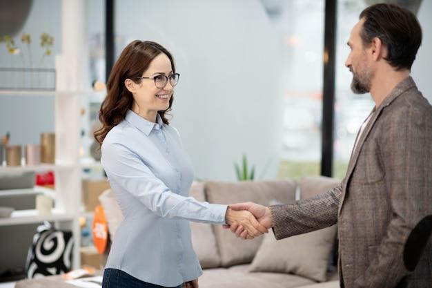 Femme gestionnaire dans un magasin de meubles rencontre un nouveau client