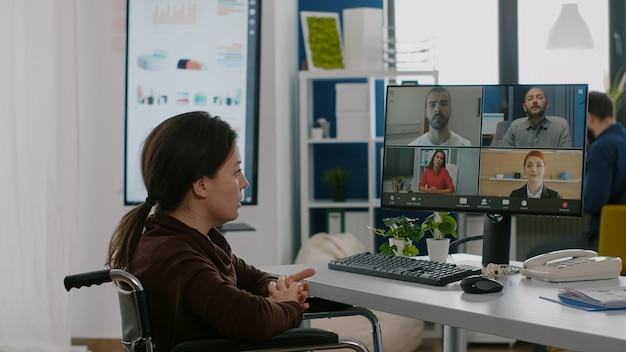 Femme gestionnaire immobilisée parlant en ligne avec un collègue à distance