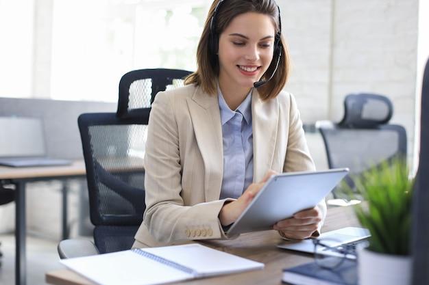 Une femme gestionnaire joyeuse assise au bureau et effectuant des tâches d'entreprise à l'aide d'une connexion sans fil sur des gadgets numériques