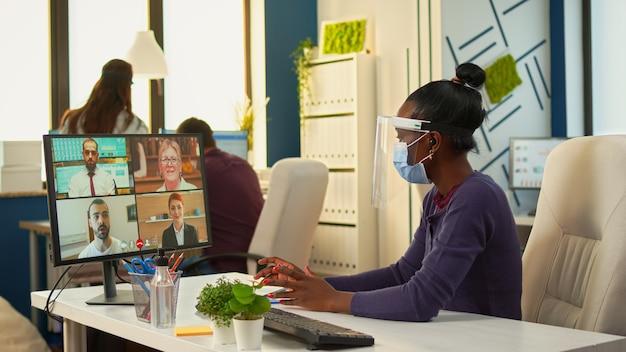 Femme gestionnaire noire avec masque de protection parlant avec des collègues à distance lors d'un appel vidéo à l'aide d'un casque sans fil. nouveau bureau d'affaires normal équipe multiethnique travaillant dans le respect de la distance sociale
