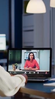 Femme gestionnaire de peau foncée parlant avec un collègue lors d'une vidéoconférence à minuit depuis le bureau d'affaires planifiant la stratégie financière