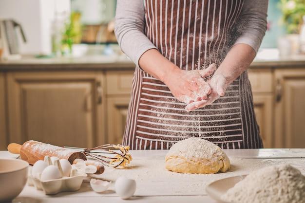 Femme gifler ses mains au-dessus de pâte agrandi. baker termine sa boulangerie, secoue la farine de ses mains, libère de l'espace pour le texte. boulangerie maison, concept de processus de cuisson