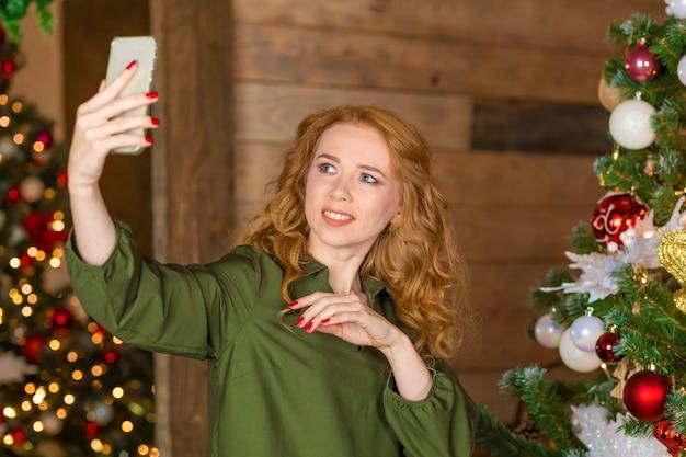 Femme de gingembre sur l'arbre de noël faisant la photo, selfie sur le téléphone. femme parlant en vidéo sur smartphone, saluant des amis, des parents à distance avec le nouvel an