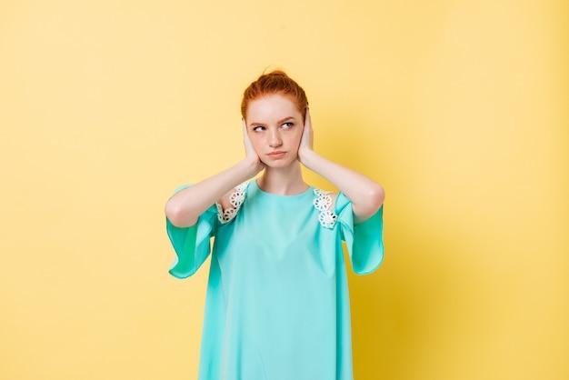 Femme gingembre confus en robe tenant la tête et en détournant les yeux