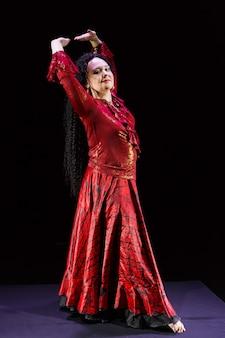 Femme gitane aux longs cheveux noirs danse avec ses mains en mouvement dans une robe rouge sur une surface noire