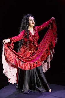 Femme gitane aux pieds nus avec de longs cheveux noirs danse en agitant une jupe rouge-noir sur une surface noire