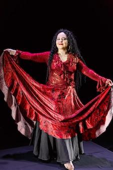 Femme gitane aux pieds nus avec de longs cheveux noirs danse en agitant sa jupe