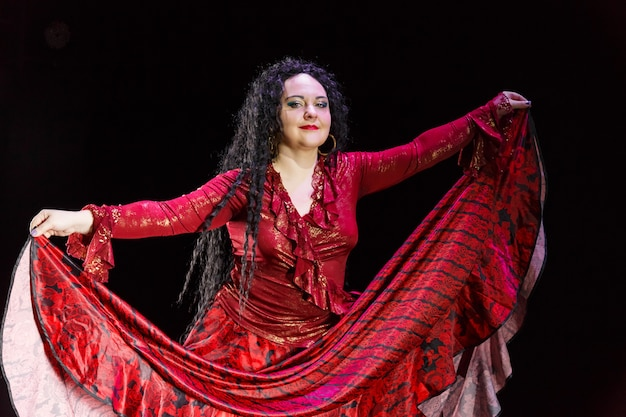 Femme gitane aux pieds nus avec de longs cheveux noirs danse dans une robe rouge sur fond noir. photo horizontale
