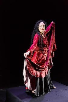 Femme gitane aux pieds nus avec de longs cheveux noirs danse dans une robe rouge sur fond noir