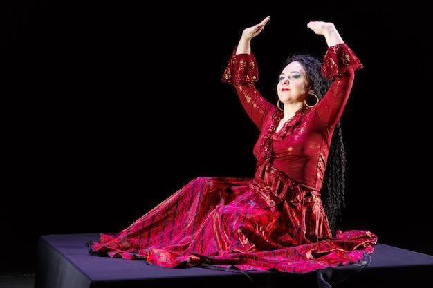 Une femme gitane aux pieds nus avec de longs cheveux noirs danse des mouvements avec ses mains dans une robe rouge sur une surface noire