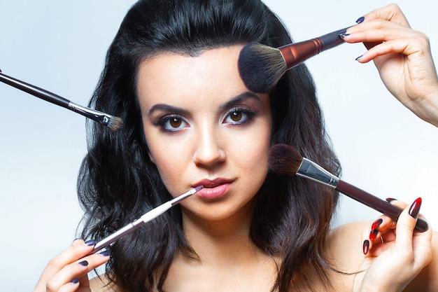 Femme glamour aux cosmétiques pour le visage.