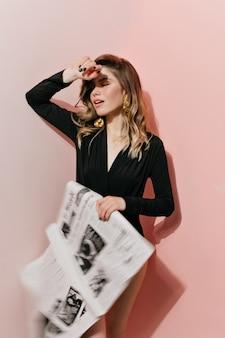 Femme glamour en body noir couvrant ses yeux