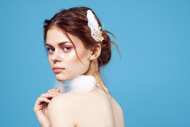 Femme glamour avec boucles d'oreilles moelleuses maquillage lumineux peau claire fond bleu