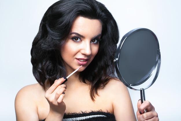 Femme glamour avec des cosmétiques pour le visage et un miroir
