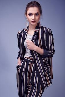 Femme glamour élégante en costume de mode posant sur fond bleu coloré