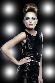 Femme glamour sur fond de projecteur