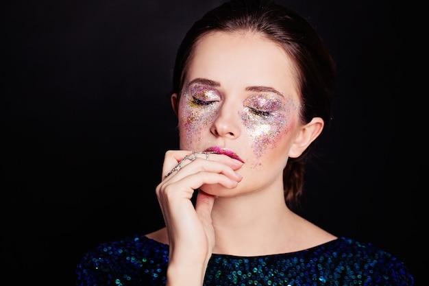 Femme glamour avec maquillage paillettes beau visage sur fond noir