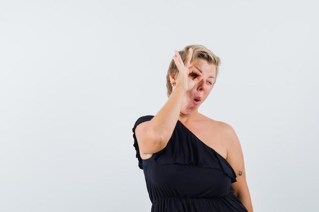 Femme glamour montrant le geste ok sur les yeux en chemisier noir et à amusé