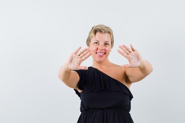 Femme glamour montrant ses paumes ouvertes en chemisier noir et à la confiance