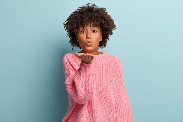 Une femme glamour à la peau sombre envoie un baiser aérien, garde les lèvres pliées, se fait couper les cheveux afro