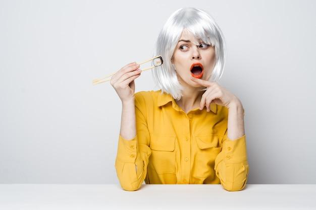 Femme glamour en perruque blanche lèvres rouges tenir des rouleaux collation avec des baguettes