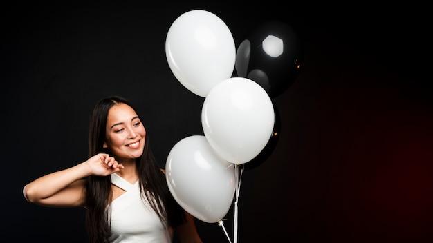 Femme glamour posant avec des ballons à la fête