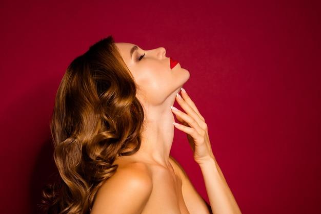 Femme glamour posant contre le mur rouge