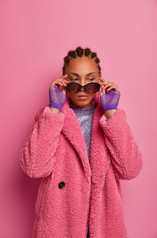 Femme glamour réfléchie avec une peau foncée saine, garde la main sur des lunettes de soleil, porte un manteau à la mode, se souvient de son dernier rendez-vous, suit les tendances de la mode, pose contre un mur rose. les gens et le style