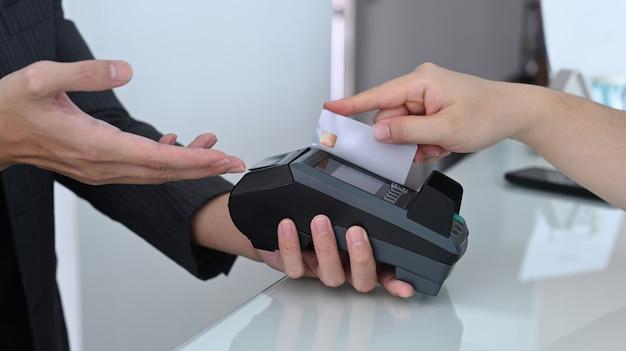 Femme glissant une carte de crédit via un terminal de paiement.