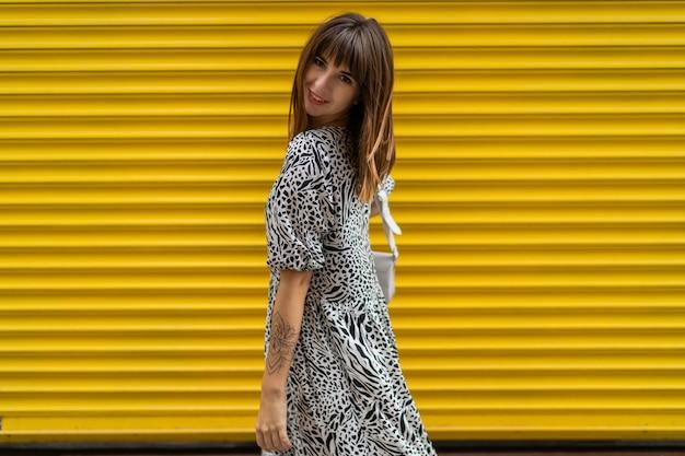 Femme gracieuse avec tatoo sur place posant sur un mur urbain jaune.
