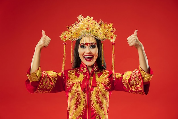 Femme gracieuse traditionnelle chinoise au studio sur fond rouge. belle fille portant le costume national. nouvel an chinois, élégance, grâce, interprète, performance, danse, actrice, concept d'émotions