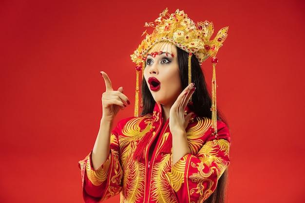 Femme gracieuse traditionnelle chinoise au studio sur fond rouge. belle fille portant le costume national. nouvel an chinois, élégance, grâce, interprète, performance, danse, actrice, concept vestimentaire