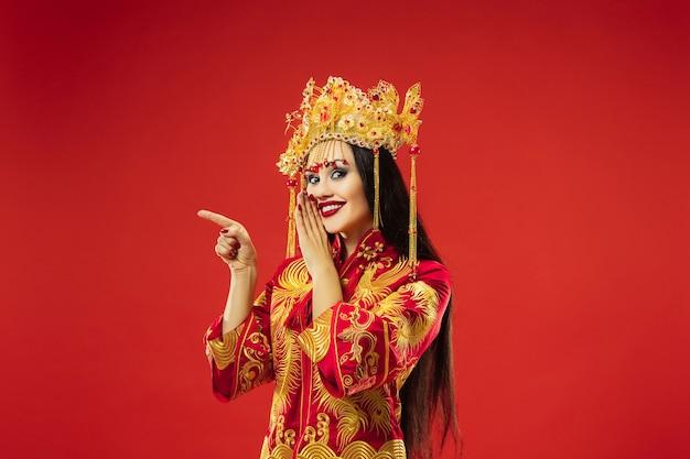 Femme gracieuse traditionnelle chinoise au studio sur fond rouge.