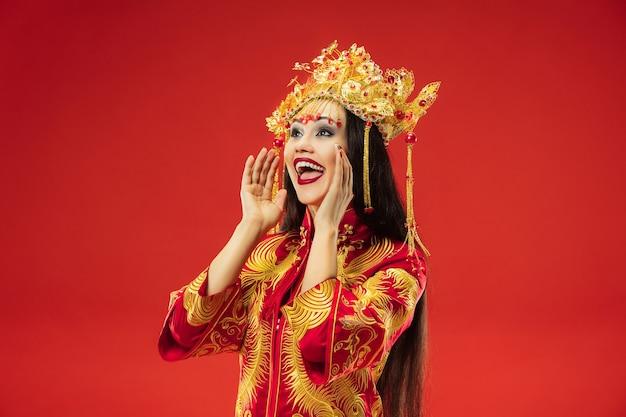Femme gracieuse traditionnelle chinoise au studio sur rouge.