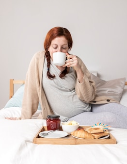 Femme grand angle bénéficiant d'un brunch au lit