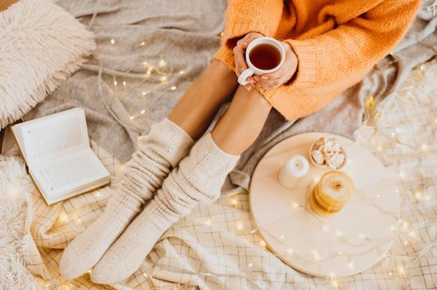 Femme grand angle profitant des vacances d'hiver avec une tasse de thé