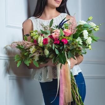 Femme avec un grand bouquet mélangé avec des rubans de tulle.