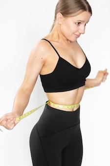 Femme avec une grande silhouette en tenue de sport a tiré son ventre autour d'elle